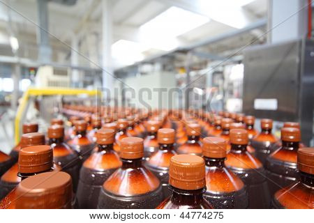 Many brown plastic bottles with beer and cap at big modern brewery.