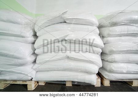 Three piles of big white sacks at large warehouse in modern factory.