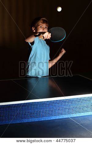 little boy wearing blue shirt playing ping pong; concentrated face; boy reflects impact