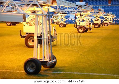 Lighting system for growing grass at empty football stadium with blue seats.