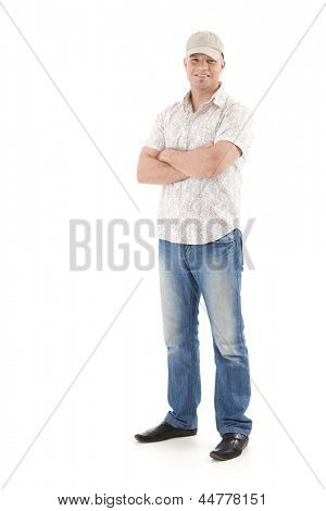 Casual summer portrait of young man wearing baseball hat, smiling, standing with arms folded, isolated on white.