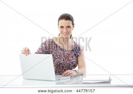 Office worker woman using laptop computer, smiling at camera, isolated on white.