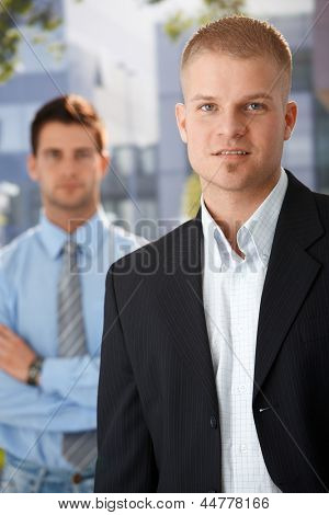 Outdoor portrait of handsome businessman standing outside of office, with colleague in background.