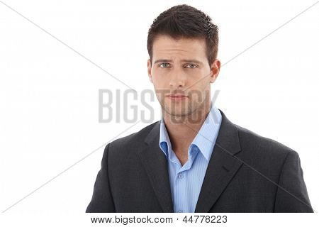 Cutout portrait of young handsome businessman, looking at camera, frowning.