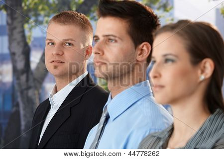 Businessman standing outside with colleagues, looking at camera confidently.