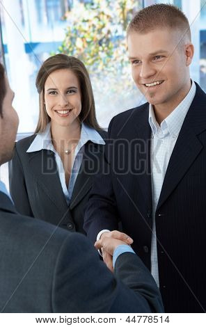 Business colleagues introducing with handshake, standing in office, smiling.