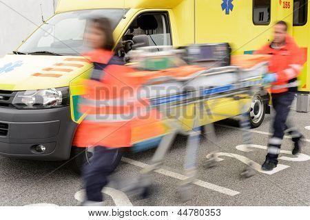 Läuft verschwommen Sanitäter team mit Tragbahre und Krankenwagen Auto