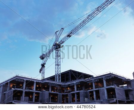Artistic photo of a crane at a construction site at sunset over blue sky