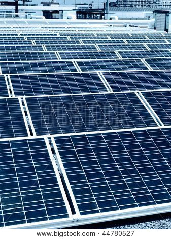 Array of solar panels in rows on a roof of a building in a city