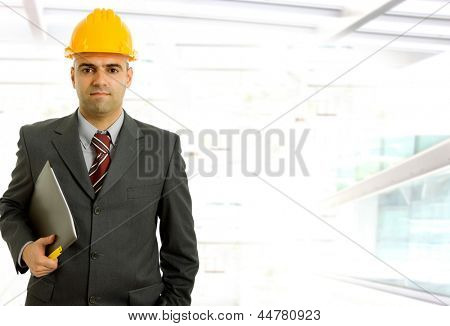 An engineer with yellow hat inside a modern building