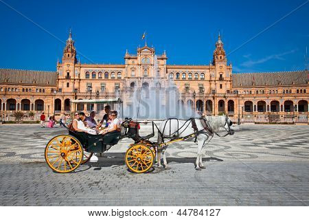 SEVILLE, SPAIN-SEP 10: Tourists enjoy a trip on horsedrawn cart on Plaza de Espana, Seville on Sep 10. 2011.