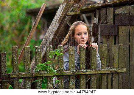 Teengirl standing near vintage rural fence.
