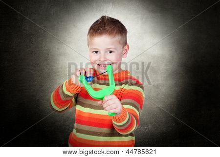 Portrait Of A Happy Boy Playing With Slingshot indoor