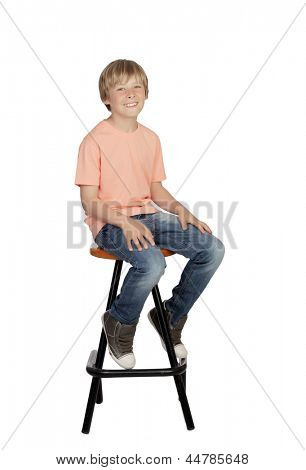 Smiling boy with orange t-shirt sitting on a stool isolated on white background