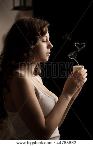 Beautiful woman with a candle in love on a black background