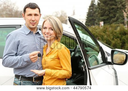 Portrait of happy beautiful couple with car keys, standing near the car