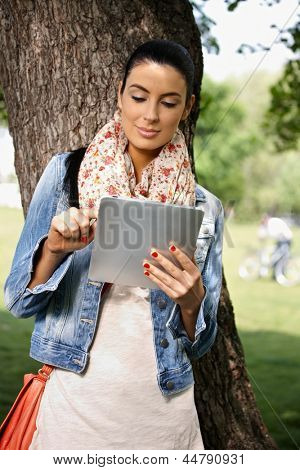 Casual young woman using tablet PC in park.