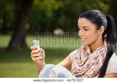 Attractive young woman using mobile, sitting in park, smiling.