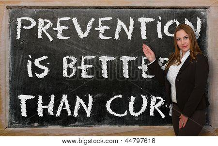 Teacher Showing Prevention Is Better Than Cure On Blackboard