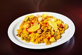A picture of a fresh home made paella served on a white plate