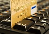 picture of internet shop  - Gold credit card on computer keyboard. Internet shopping. Focus on 4 number