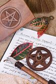 stock photo of pentacle  - wooden pentacle with incense burning with hand written book of shadows and fall leaves  - JPG