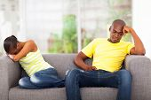 stock photo of conflict couple  - young african couple having conflict sitting on the sofa - JPG