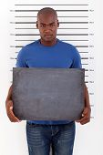 stock photo of mug shot  - young african man holding a black board police mug shot - JPG