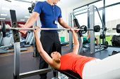 stock photo of bench  - Woman with her personal fitness trainer in the gym exercising with dumbbells - JPG