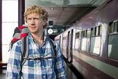 stock photo of squinting  - Young man with a backpack ready to embark on a journey by train - JPG