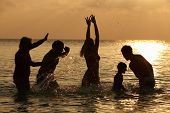 Silhouette Of Multi Generation Family Having Fun In Sea