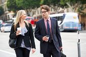 stock photo of takeaway  - Businessman And Businesswoman In Street With Takeaway Coffee - JPG