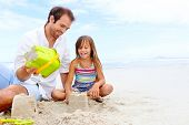 pic of love making  - happy healthy family father and daughter building sand castle on the beach smiling and carefree - JPG
