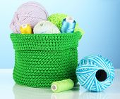 Colorful yarn for knitting in green basket on blue background