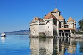 World-wide well-known Ch?????????????teau de Chillon on Lake Geneva. The white tourist motor ship floats by a magnificent medieval castle poster