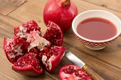 Cut pomegranate on a wooden table with bowl of juice