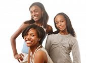 Three happy African American teenage girls on white background. Selective DOF, focus on the girl in