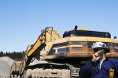 pic of jcb  - building engineer with giant bulldozer in background - JPG