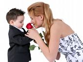 Adorable Boy Smelling Rose With Beautiful Teen Girl poster