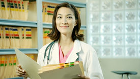 stock photo of medical office  - a medical assistant looks over a patient - JPG