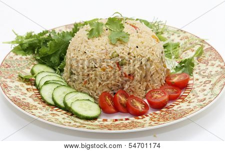 A healthy tomato (thakkali) biriyani with a salad of cucumber, cherry tomatoes and some fresh leaves. This biryani, which incorporates onion, peas and a capsicum  ball pepper, is a South Indian dish.
