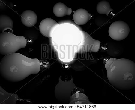 Idea Concept. One Glowing Light Bulb Standing In Front Of Unlit