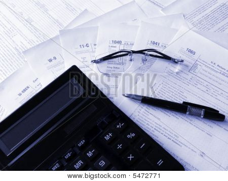 Formas de impuestos, calculadora, lápiz y gafas