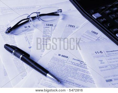 Calculadora, pluma, gafas y formas de impuestos