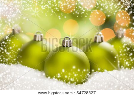 Beautiful Matt Green Christmas Ornaments on Snow Flakes Over an Abstract Snow and Light Background with Room For Your Own Text.