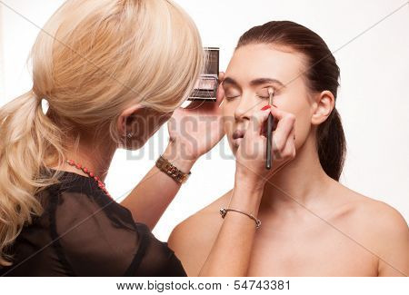 Beautician applying eye makeup to an attractive young model with bare shoulders as she prepares for a photo shoot, isolated on white
