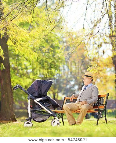Grandfather sitting on a bench and looking at his baby nephew in a stroller, in a park, shot with a tilt and shift lens
