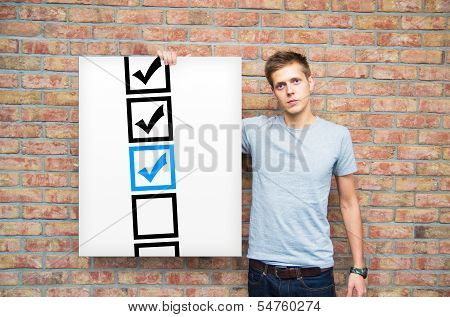 Young Man Holding Whiteboard With Check Boxes