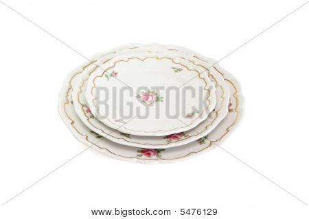 Stack Of Three White Plates And Saucers With Flowers Solated