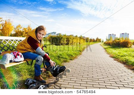 Boy On The Bench Putting On Roller Skates